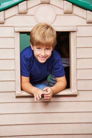 playhouse: Smiling boy looking through window in a playhouse in kindergarten