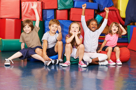 Children cheering together after victory in gym of a pre school Stock Photo
