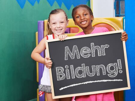demanding: Two children demanding on blackboard in German Mehr Bildung (More education)