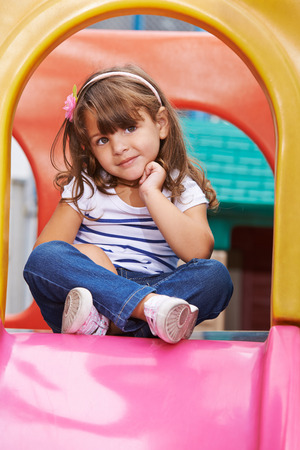 tailor seat: Girl sitting in tailor seat on a slide in a playground Stock Photo