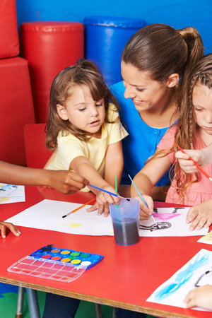 art lessons: Children painting images in child care after elementary school with teacher Stock Photo