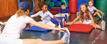 school nurse: Children doing gymnastics in gym of preschool with nursery teacher