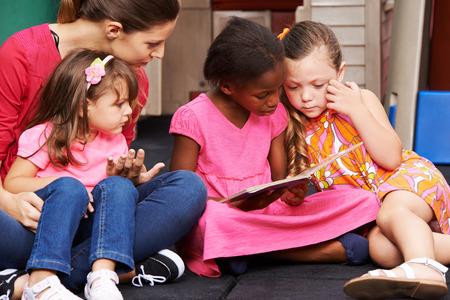 Groep kinderen en opvoeder met prentenboek in een kleuterschool