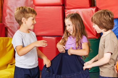 Drie kinderen opruimen samen in een kleuterschool sportschool