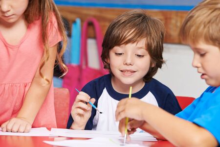 elementary school: Children painting images with water color in art class in elementary school