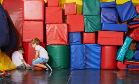 Droevig kind zitten in de hoek van een fitnessruimte en een jongen probeert hem te troosten