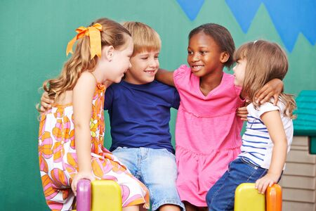 Happy children laughing and sitting together in kindergarten