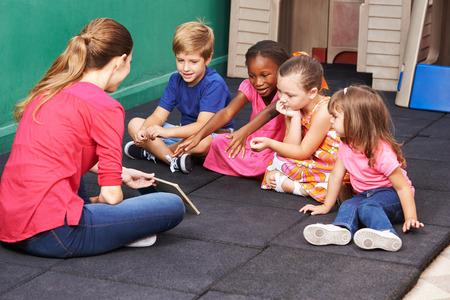 Groep jonge geitjes spreken over boek met kleuterleidster in kleuterschool