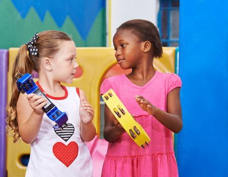 Kinderen spelen tamboerijnen in het begin van muzikale opvoeding in de kleuterschool Stockfoto