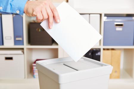 encuestando: Mano con papeleta de votación y la cabina de elección en la mesa de votación