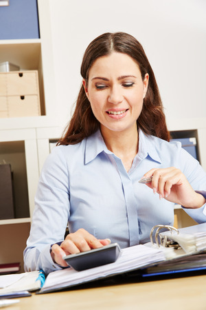 examiner: Business woman inf office analyzing files with a calculator at her desk