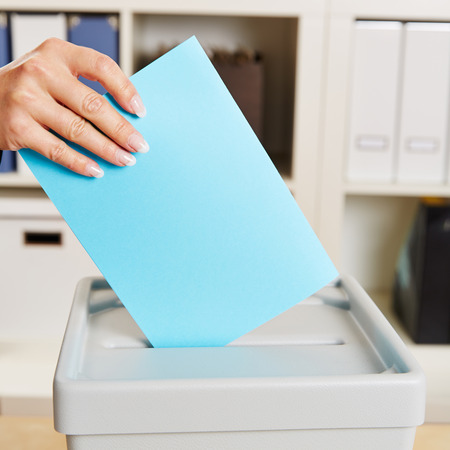 local election: Hand with ballot paper for voting in an federal election Stock Photo