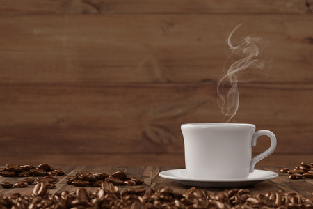 Vapor en la taza de café recién hecho con las habas en una mesa de madera (3D) Foto de archivo