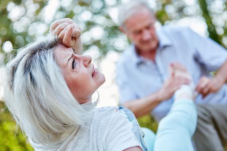 pies: Mujer mayor con dolor en el pie, mientras que el hombre pone una venda en él Foto de archivo