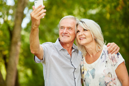 Senior couple taking a selfie with smartphone in summer in the nature