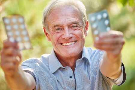 medicament: Senior man holds medicament with joy in the nature