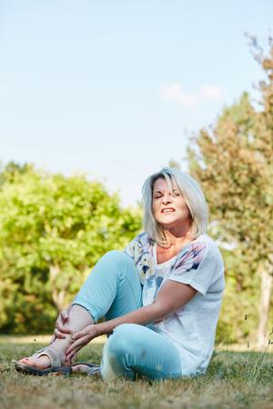 痛みを持つ古い女性は、自然の中で彼女の足を保持しています。 写真素材