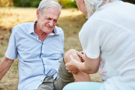 Old man with pain on his knee and woman gives him first aid