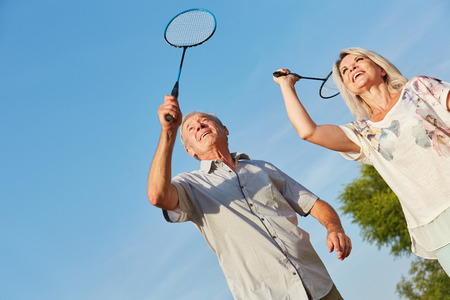 Happy senior couple playing badminton togheter as a team in summer Stock Photo