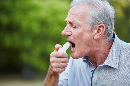 Old man using a spray as a medicine for hay fever in nature Stock Photo