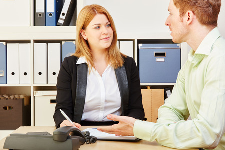 financial advice: Tax consultant giving financial advice to a man in an office