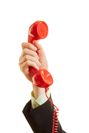 cry for help: The hand of a man holding a red telephone in the air