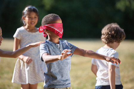 Children playing blind man's buff in summer and having fun Banco de Imagens - 64920070