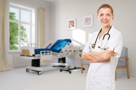 outpatient: Smiling female senior doctor in hospital room with single bed