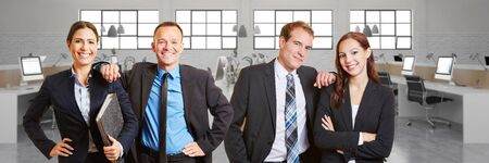 servicing: Happy Business people team in front of office space with computers Stock Photo