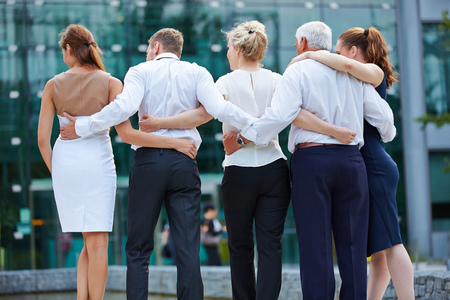 team from behind: Group of business people embracing from behind and looking to office