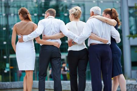 Gruppe Geschäftsleute, die von hinten und auf der Suche nach Büro umarmen Standard-Bild