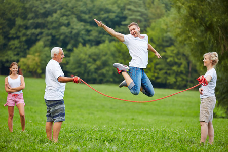Happy man jumping high while rope skipping in nature