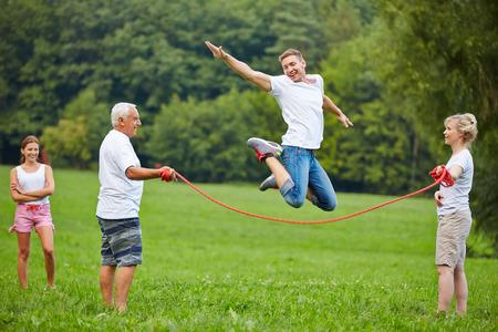 Heureux l'homme sautant de haut tandis que la corde à sauter dans la nature