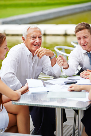 team communication: Communication in a business team during a meeting outdoors at a table