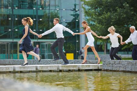 colleagues: Business team running as a chain in a row with holding hands