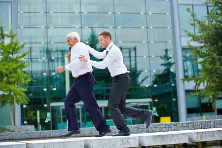 corporate office: Two happy businesspeople jogging together in city in front of an office building