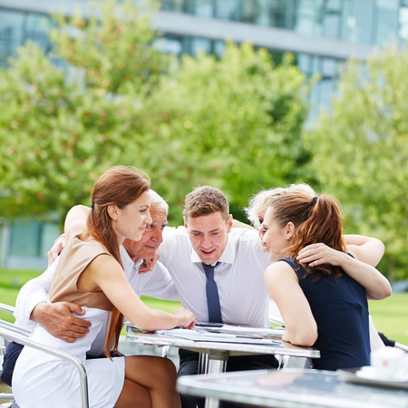 company secrets: Business team hugging for motivation in a meeting outdoors Stock Photo