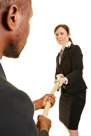 opponents: Two business people as opponents while playing tug of war Stock Photo