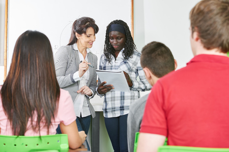 school classroom: Teacher helps a student with her presentation in a high school classroom Stock Photo