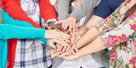 clique: Team of students put their hands together to motivate themselves Stock Photo