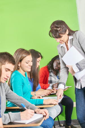 Women supervises a test for a high school class Stock Photo