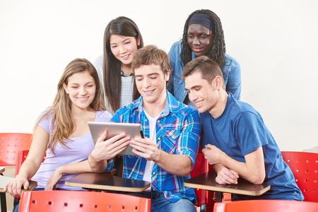 estudiantes universitarios: Estudiantes felices con la tableta en su salón de clases en la universidad