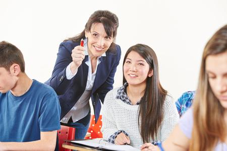Profesor sonriente ayuda a un estudiante durante una prueba y le da una propina Foto de archivo
