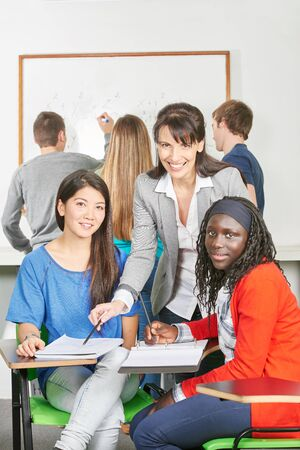 lecturer: Girls learning together doing teamwork with their teacher Stock Photo