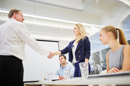 succesful: Manager gratulates succesful businesswoman in a business meeting
