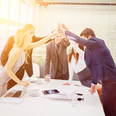 Business people give each other a high five in the office