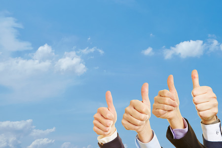 Group with thumbs up in the air under the sky Stock Photo