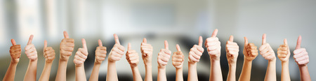 likeable: Many hands holding thumbs up in office Stock Photo