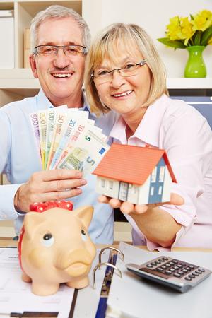 dinero euros: Mayor feliz pareja de ahorro cuentas de dinero euro durante financiación de la vivienda