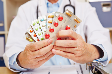 Doctor holding many prescription drugs in his hands